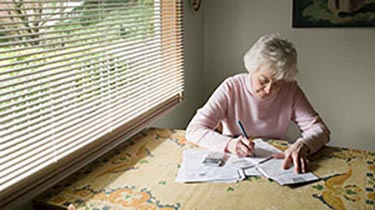 Woman looking at paperwork at her kitchen table
