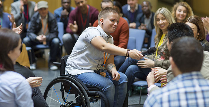 Young man in a wheelchair handing a microphone to someone